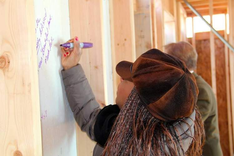 Angela Clemmons, of Madison, not only volunteered in the Dancing with the Stars fundraiser, helping to raise $60,000, she also visted with the family at the groundbreaking and left a message of good will and support on the walls. Photo courtesy of Raise the Roof