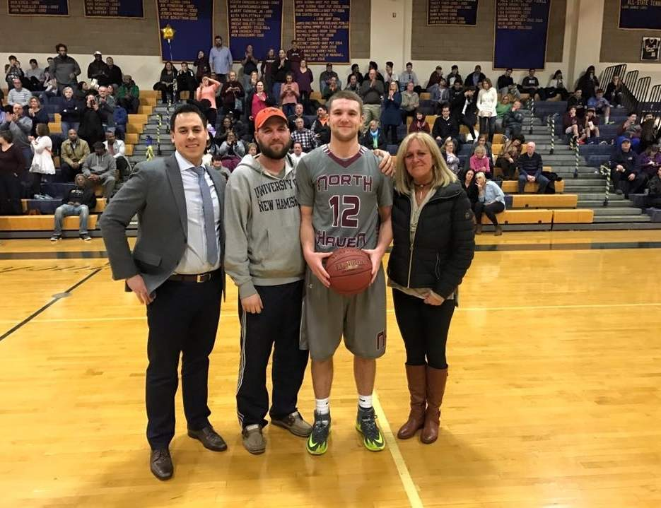 Senior Jack Steinman joined the 1,000-point club when the North Haven boys' basketball team posted a 64-52 win at East Haven on Feb. 20. Pictured Indians' Head Coach Justin Falcon, Steinman's brother Joe Carasone, Steinman, and his mother Linda Steinman. Photo courtesy of Linda Steinman