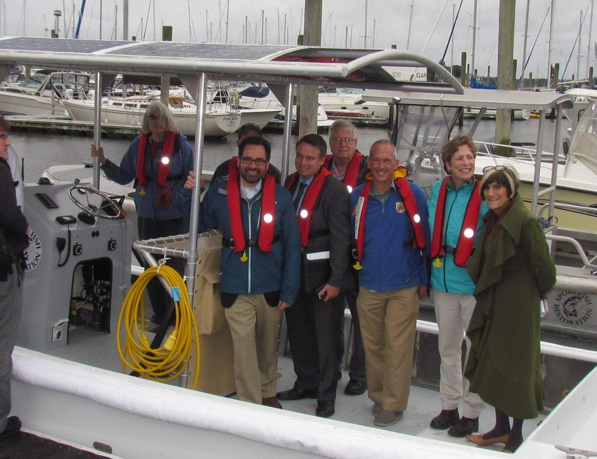Ready to take a trip on the world's first full-sized, fully electric solar powered pump out boat in Branford are federal state and local leaders including CT DEEP Commissioner Robert Klee (at rail, left) and US Congresswoman Rosa DeLauro (far right) together with U.S. Fish and Wildlife Regional Director Wendi Weber (next to DeLauro) and other representatives of agencies and organizations which assisted East Shore District Health Dept. with the vessel program.   Pam Johnson/The Sound